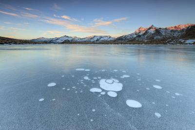 https://imgc.allpostersimages.com/img/posters/ice-bubbles-on-the-frozen-surface-of-andossi-lake-at-sunrise-spluga-valley-valtellina-italy_u-L-Q12SB100.jpg?p=0