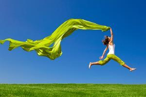 Beautiful Young Woman Jumping On A Green Meadow With A Colored Tissue by iko
