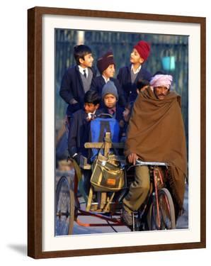 Indian Children Ride to School on the Back of a Cycle Rickshaw