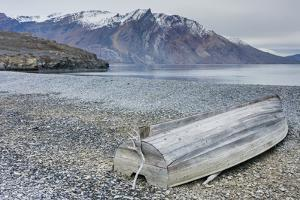 Greenland, Kong Oscar Fjord. Ella Island. Weathered boat on the shore. by Inger Hogstrom