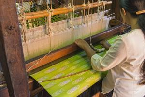 Myanmar. Shan State. Inle Lake. Woman weaving silk at a wooden loom. by Inger Hogstrom