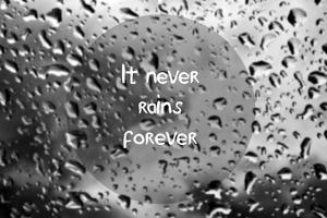 Inspirational Quote with Words it Never Rains Forever on Blurred Natural Background with Water Drop
