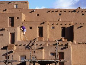 A Woman Climbs a Ladder to an Apartment in an Adobe Complex by Ira Block