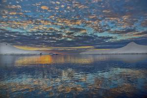 A Beautiful Seascape of Puffy Little Clouds Reflected in Icy Water at Sunset by Ira Meyer