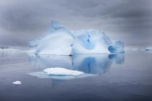 A Blue Iceberg under Cloud-Filled Skies, in Glassy Calm Water by Ira Meyer