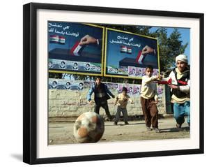 "Iraqi Boys Play Soccer Below the Poster Reading ""To Grant Iraqi Children Better Iraq"""
