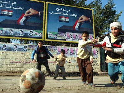 "Iraqi Boys Play Soccer Below the Poster Reading ""To Grant Iraqi Children Better Iraq"""