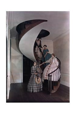 Women Walk Down a Spiral Staircase in an Ancestral Home by J. Baylor Roberts