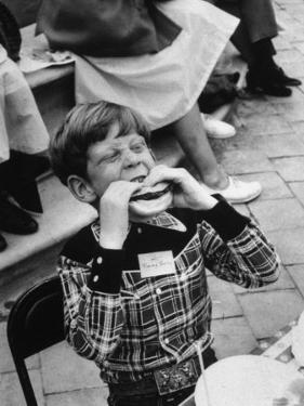 Hollywood Child Timmy Garry at Children's party Dressed in Cowboy Outfit eating a Hamburger by J. R. Eyerman