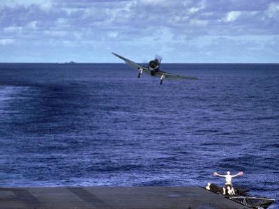 Landing Signal Officer Communicating with American Pilot Preparing to Land on Palau Islands by J. R. Eyerman