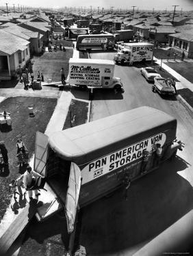View of Newly Built Houses Jammed Side by Side, Divided by a Street Clogged with Moving Vans by J. R. Eyerman
