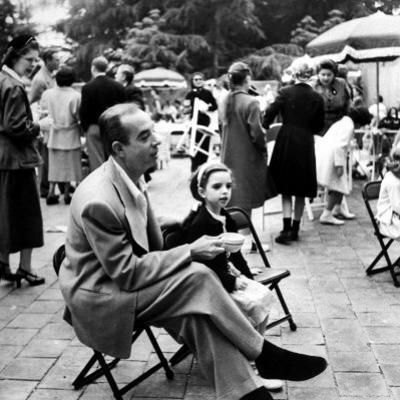 Vincente Minnelli with coffee sitting in chair with Daughter Liza at Outdoor Children's Party Being by J. R. Eyerman