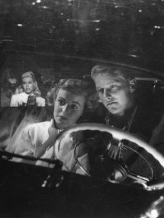 Young Couple Snuggling in Convertible as They Intently Watch Movie at Drive-in Movie Theater by J. R. Eyerman