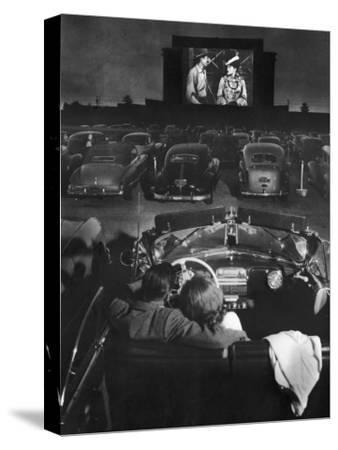 Young Couple Snuggling in Convertible as They Watch Large Screen Action at a Drive-In Movie Theater by J. R. Eyerman
