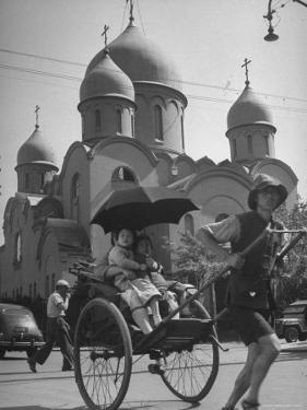 Family Being Pulled in a Rickshaw with a Russian Orthodox Church in the Background by Jack Birns