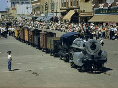 People Watch a Miniature Train Parade on Main Street