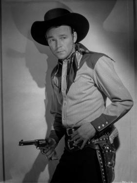 Roy Rogers Leaning on Wall and Holding a Revolver by Jack Freulich