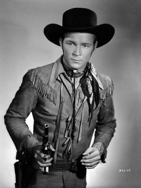 Roy Rogers posed in Cowboy Outfit and Holding a Gun by Jack Freulich