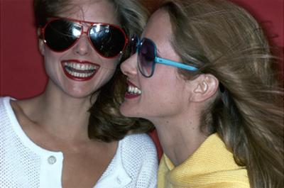 Close-Up on Two Models with Smiles, a Pair of Red Plastic Bon-Lon Sunglasses by Bonneau