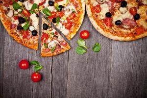 Delicious Italian Pizzas Served on Wooden Table by Jag_cz