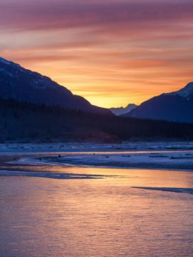 An Orange Sunrise over the Chilkat River Contrasts with the Icy Blue Mountains by Jak Wonderly