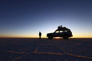 Toyota Land Cruiser Silhouetted Against Sunrise, Salar De Uyuni, Bolivia by James Brunker