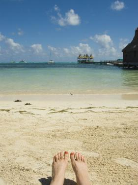 Womens Feet on the Beach with a View of the Ocean, Pier and Boats, Ambergris Caye, Belize by James Forte