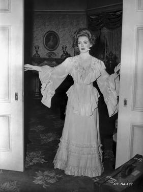 Bette Davis Posed in White Long Sleeve Ruffled Long Dress by James Kerbe