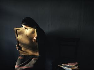 A Grieving Woman Holds a Photograph of Her Murdered Son by James L. Stanfield