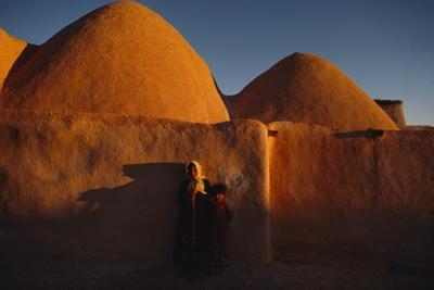 A woman and child dwarfed by mud brick beehive huts at dawn. by James L. Stanfield