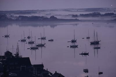 Yachts anchor in fog-shrouded Nantucket Harbor. by James L. Stanfield