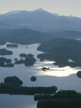 A Floatplane Flies over Long Lake with Mount Marcy in the Background by James P. Blair