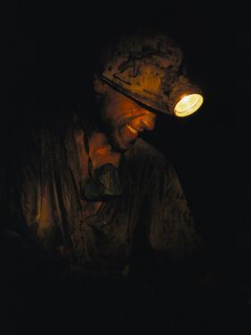 A Miner with a Head Lamp Works Inside the Csa Coal Mine at Karvina by James P. Blair