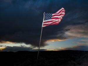 American Flag Blowing in Wind at Dusk in the Desert by James Shive