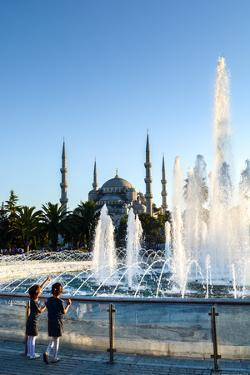 Two Young Turkish Girls Pointing to the Blue Mosque, UNESCO World Heritage Site by James Strachan