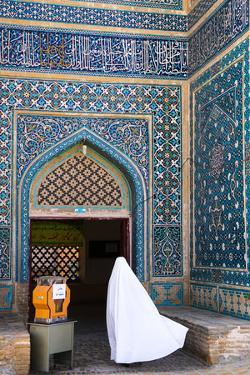 Woman in white chador enters Jameh Mosque, Varzaneh, Iran, Middle East by James Strachan