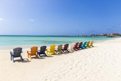 A Row of Colourful Wooden Deckchairs on Palm Beach, Aruba, Netherlands Antilles by Jane Sweeney