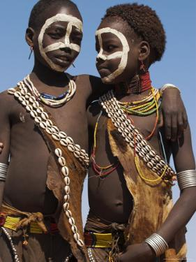 Two Hamer Girls Wearing Traditional Goat Skin Dress Decorated with Cowie Shells, Turmi, Ethiopia by Jane Sweeney