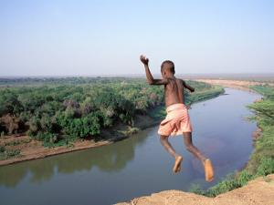 Karo Boy Leaps Off a Cliff Over the Omo River, Ethiopia by Janis Miglavs