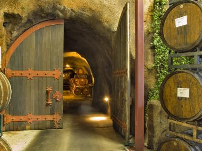 Oak Barrels Stacked Outside of Open Door To Aging Caves at Ironstone Winery, California, USA by Janis Miglavs