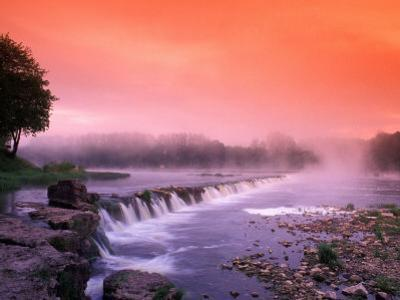 Sunrise in the morning mist over the waterfall on the Venta River near Kuldiga, Latvia by Janis Miglavs
