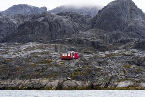 A Bright Red Cottage on the Rugged and Brutal Rock Shoreline of a Fjord by Jason Edwards