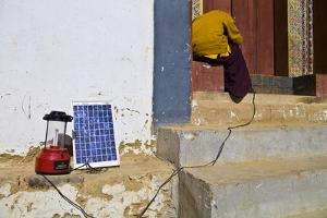A Buddhist Monk Attempts to Fix a Solar Panel to Charge His Cell Phone and Camping Lamp by Jason Edwards