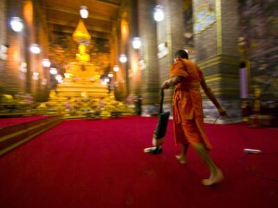 A Buddhist Monk Vacuums the Chapel's Red Carpet after Evening Prayer