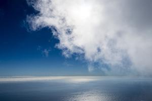 A Cloud Bank Descending over Calm Blue Ocean by Jason Edwards