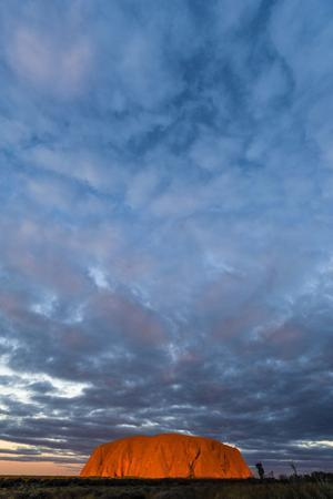 A Cloud Bank from an Approaching Storm Turns Magenta as it Shrouds Uluru and the Desert Plain