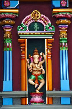A Colorful Statue of Ganesh Standing Between Pillars on a Temple Wall by Jason Edwards
