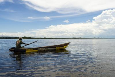 A Fisherman Paddling a Canoe on a Wide African River by Jason Edwards