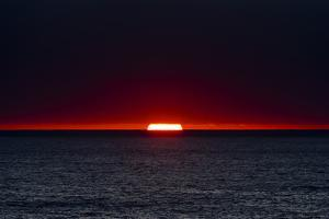 A Slither of Sunlight Pierces a Storm Cloud Above a Darkened Ocean at Sunset by Jason Edwards