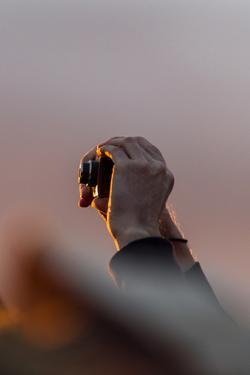 A Tourist Holds His Digital Camera Above a Crowd to Capture the Sunrise over the Desert and Uluru by Jason Edwards